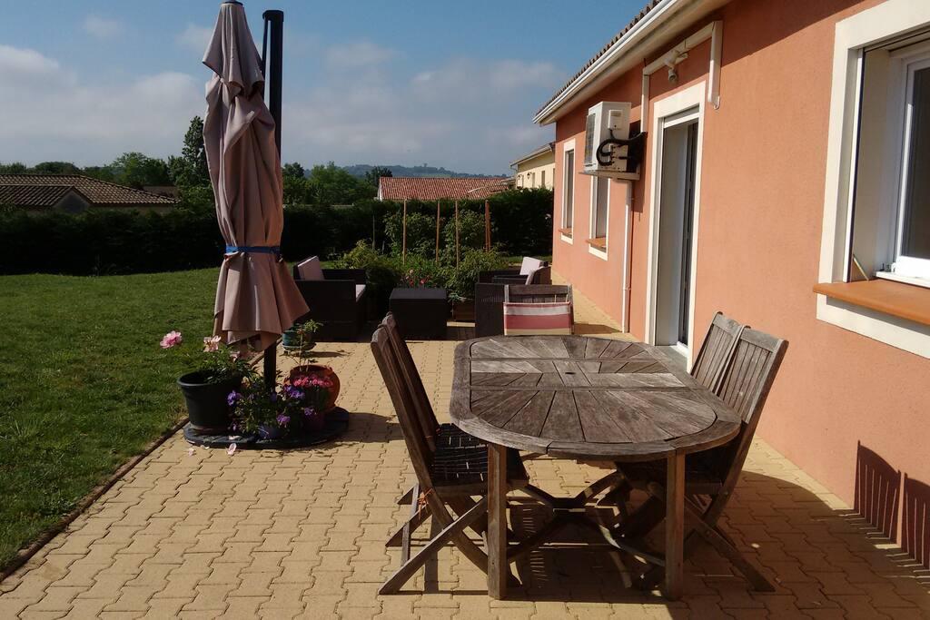 la terrasse avec la table et le petit salon de jardin derrière. en fond, le potager