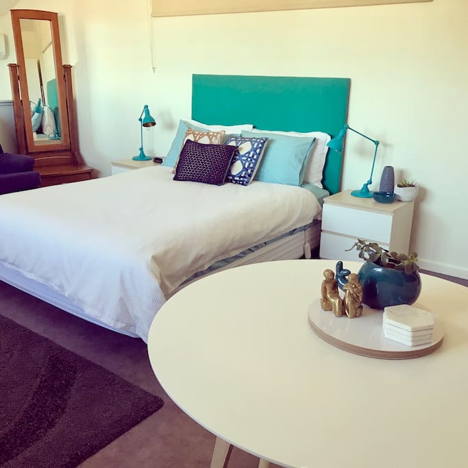 Guest suite with table, seating, full length mirror, bedside table/lamps, alarm clock and couch