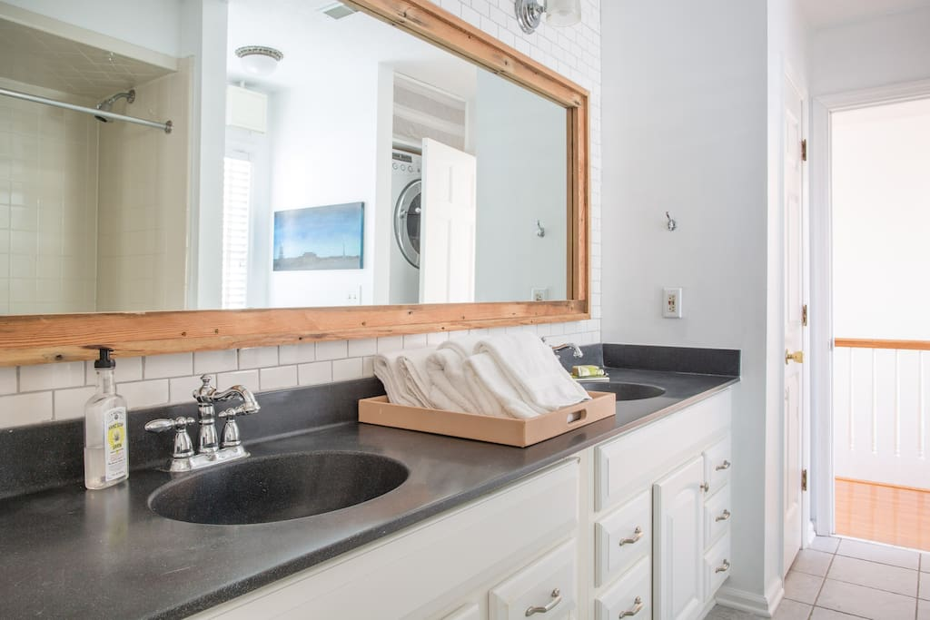 The en-suite bathroom features double sinks, complimentary toiletries, and fluffy towels