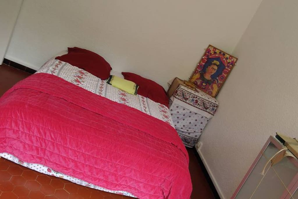 Une grande chambre donnant sur le jardin comprenant un lit deux places et une grande armoire dressing