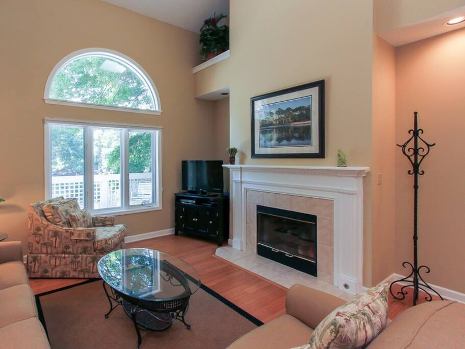 The living room in 7640 Huntington has flat panel TV and large windows overlooking the lagoon