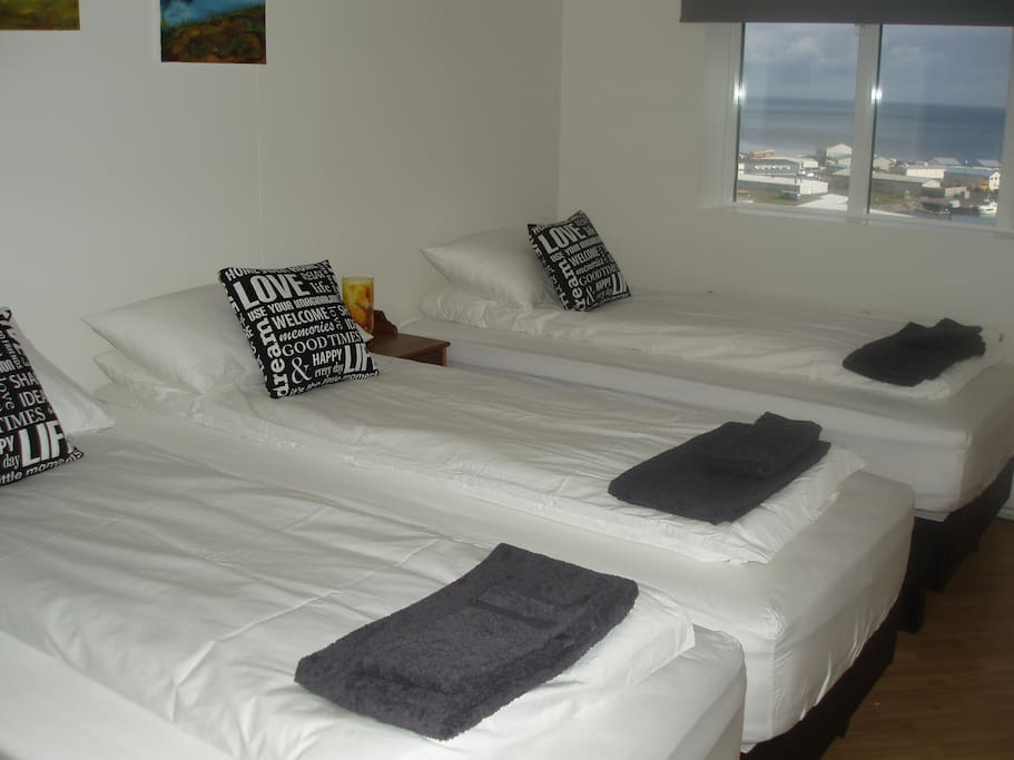This is a three person room with made up beds and a great view of the harbor and up to the mountains.