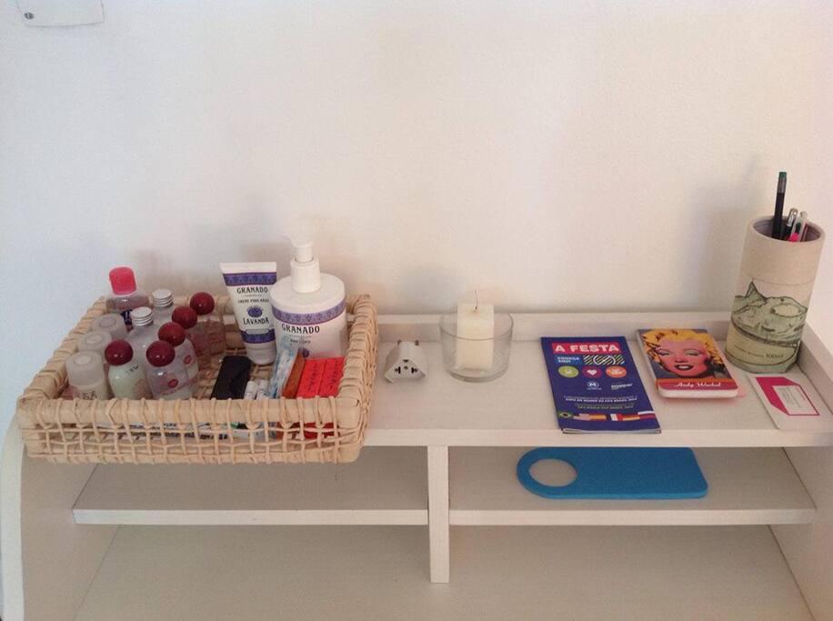 Cestinha com higiene pessoal: Shampoo, Condicionador, Sabonete líquido, Hidratante Corporal, Cotonete, Absorvente e Pente para Cabelo.  Ao lado, caneta, lápis, bloco de anotações, guia do metrô Rio.