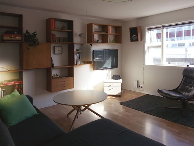 Living room with sofa area, tv and desk.