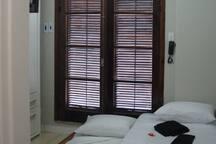 """As 2 camas de solteiro; a inferior, no chamado estilo """"gaveta"""", vistas a partir da porta de entrada INDIVIDUAL & PRIVATIVA;  ao fundo, as portas duplas de acesso ao terraço."""