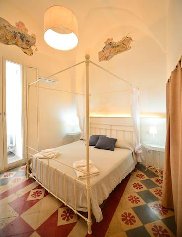 La stanza matrimoniale con affreschi e cementine originali - The master bedroom with frescos and vintage cement floor tiles