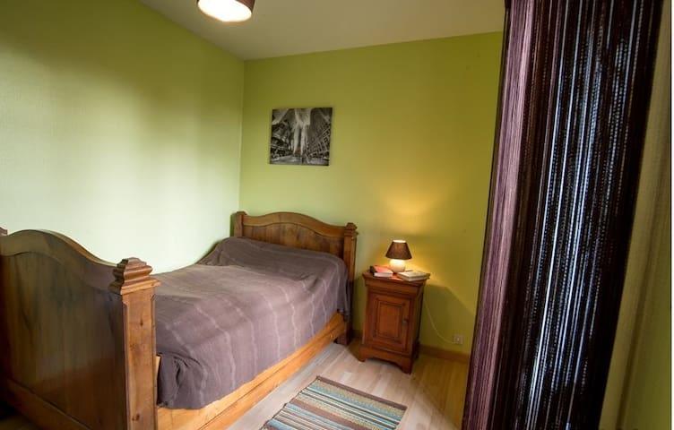 Chambre avec un lit simple et une commode.