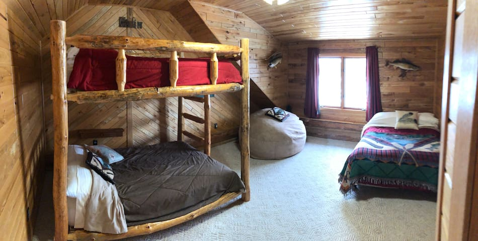 This Upstairs bedroom has a full sized Log  bunk Bed can sleep 4 adults and a Queen bed in this room beautiful total of 6 can sleep, beautiful view of the lake from this room as well.