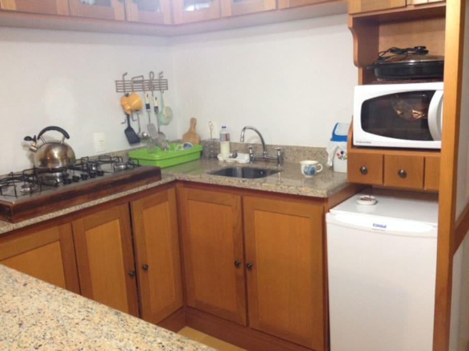 Cozinha com microondas, forno, frigobar e fogão.
