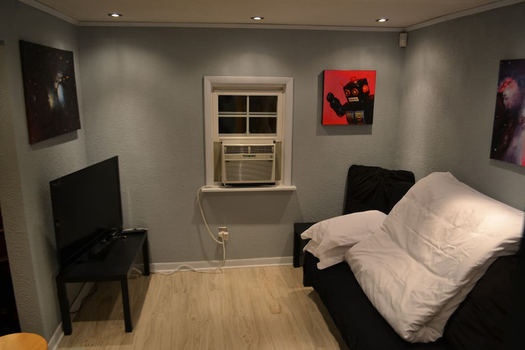 Bedroom with TV and artwork including local artwork and hubble space canvas prints.