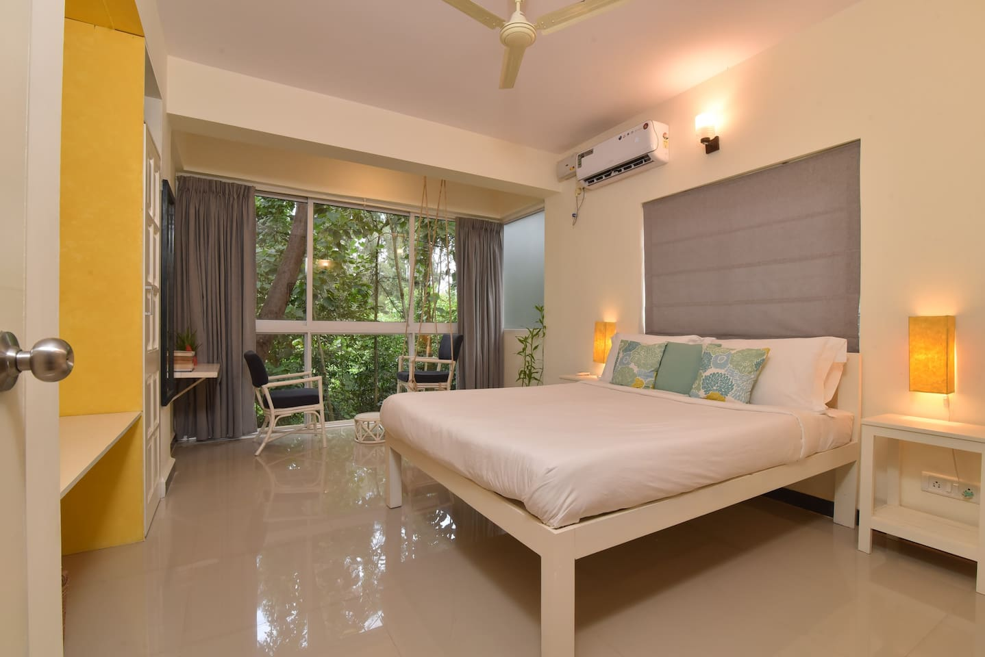 Relax and rejuvenate in the bedroom with full glass windows looking out upon lush green forest.