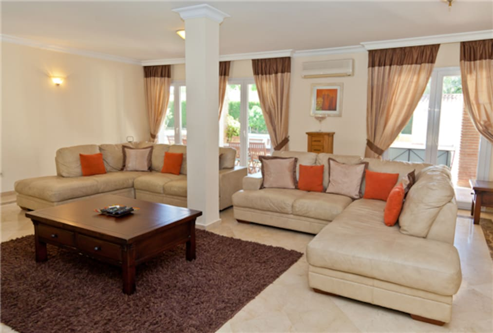 Large modern lounge with high quality leather sofas and garden terrace access