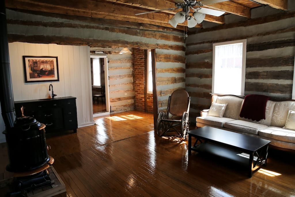The spacious living room has vintage and antique funiture and a small sink.