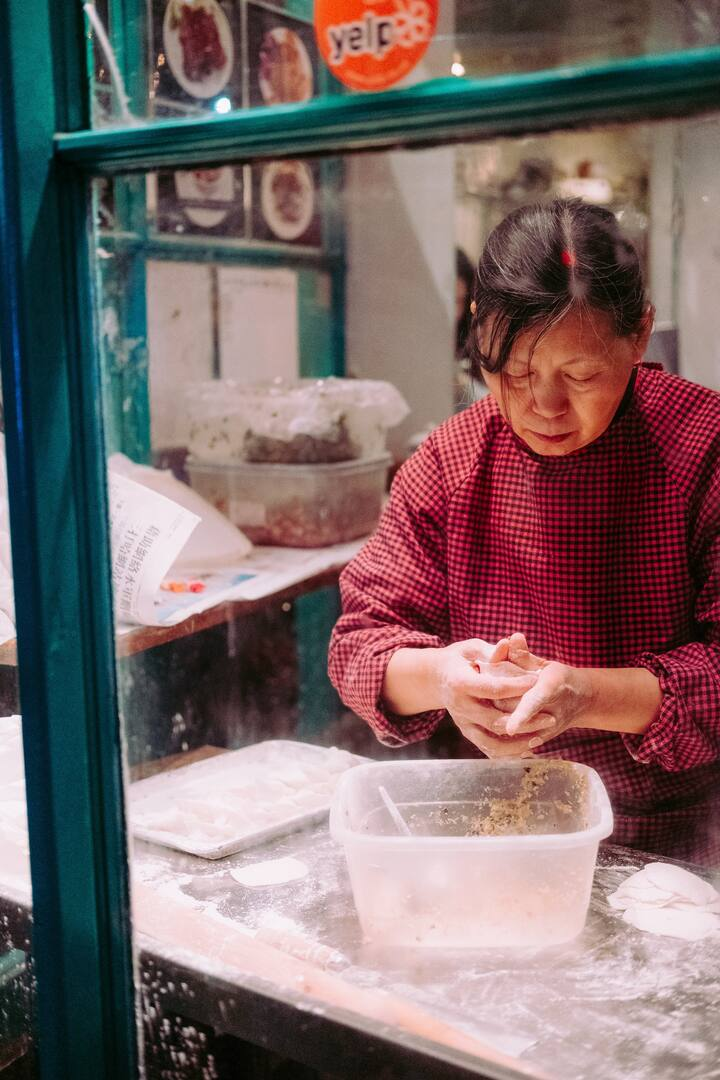 A restaurant owner making dumplings