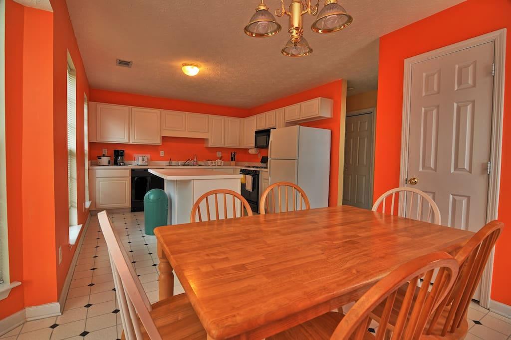 Full stocked kitchen with gas stove, oven, microwave, dishwasher and kitchen island. In the forefront the dining table with 6 chairs