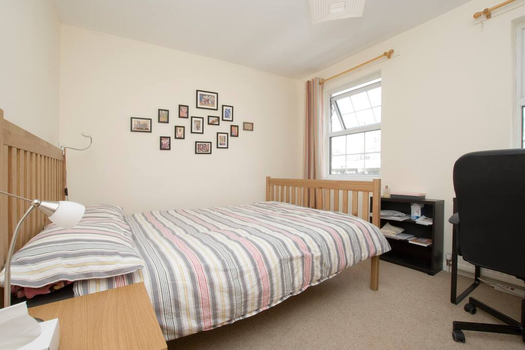 Guest bedroom; comfortable double bed, bookcase and two windows.