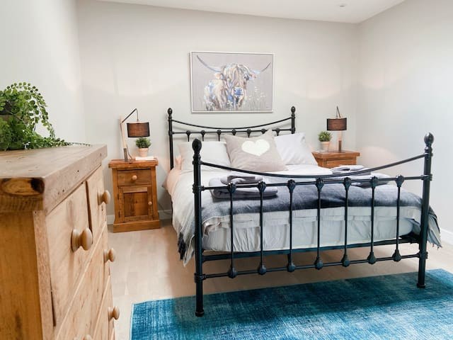 Master bedroom with double bed, bedside tables, chest of drawers and dressing area with dressing table and clothes rail.