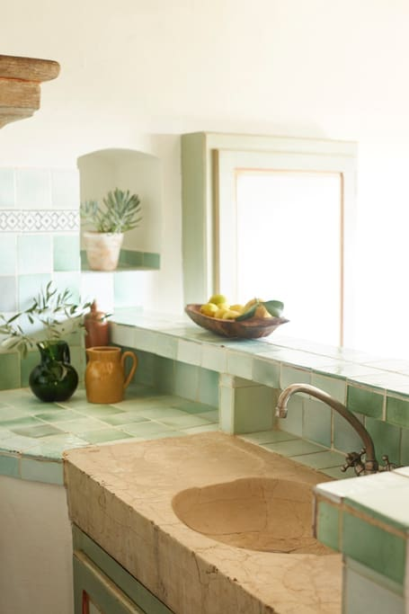 Green tile backsplash and countertop in a French Country kitchen #Frenchcountry #kitchendesign #kitchentile