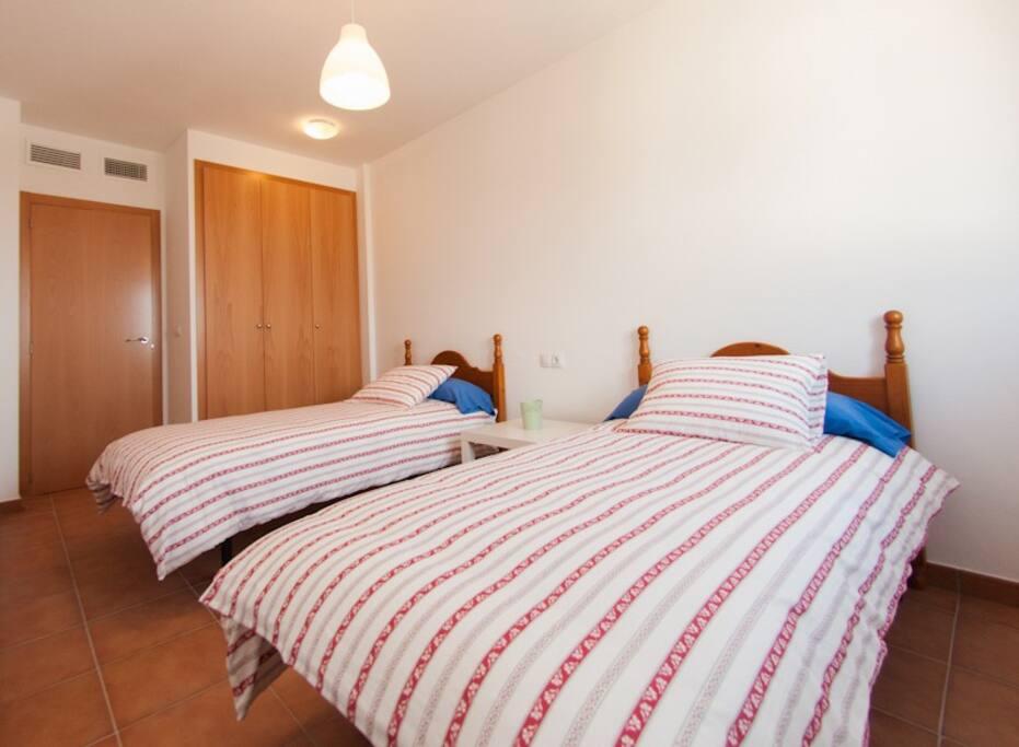 Dormitorio doble con vistas al mar y la montaña.
