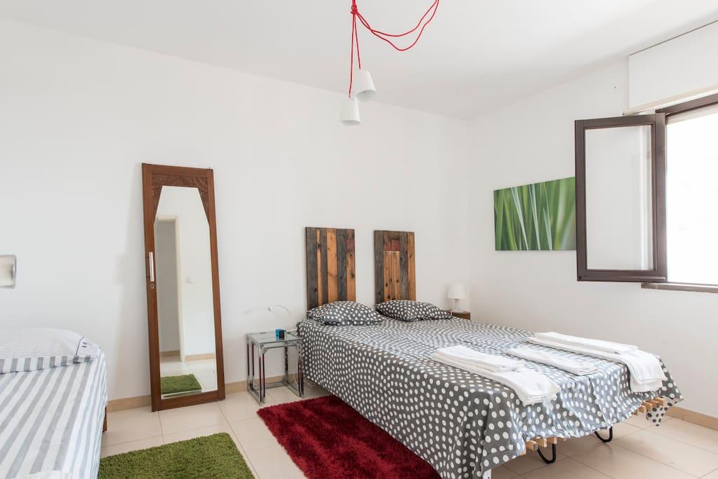 Quarto com colchão King e 2 camas individuais, ideais para crianças.