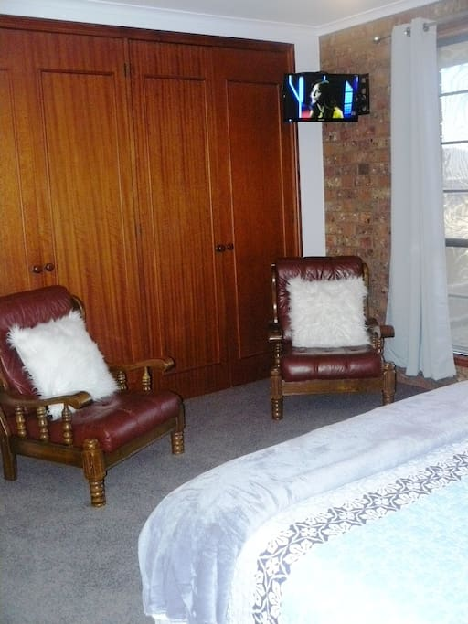 TV plus two armchairs in bedroom