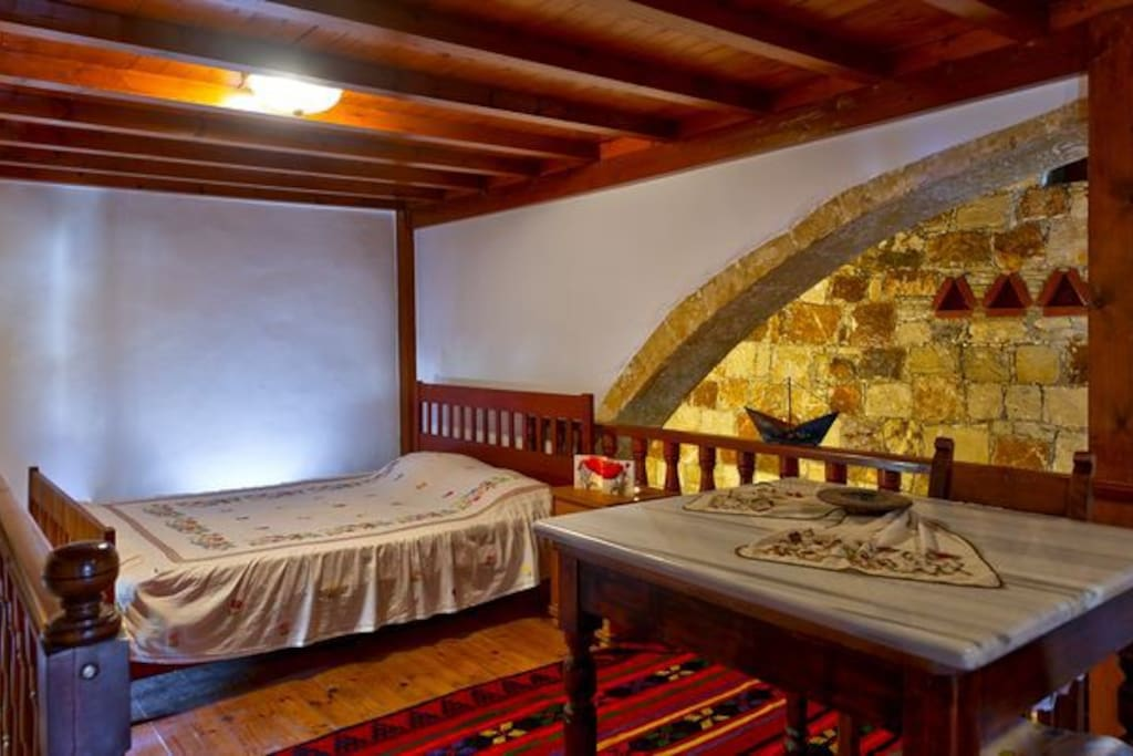 Queen size bed at the attic. wooden floor and ceiling. Exit at a small terrace