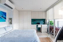 Light and airy bed area with desk for working and  powerful Daikin air-conditioner.