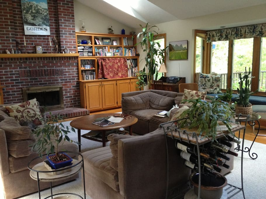 Spacious Great room with many  windows and seating near deck Comfortable chairs, fireplace.