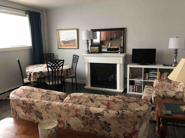 Bright and comfortable living room and dining area has dining area for 4 and an eating bar, a single hideabed loveseat, large DVD selection with screen, comfortable chair and fireplace.