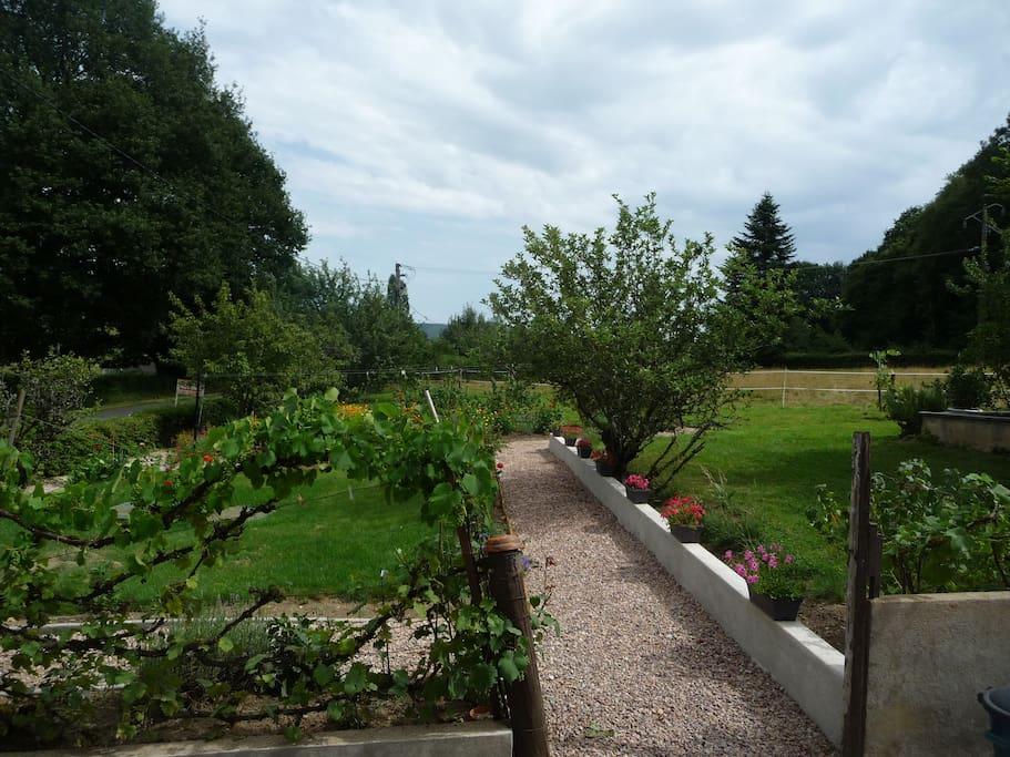 le jardin fleuri devant la maison, avec grand terrain pour s'amuser