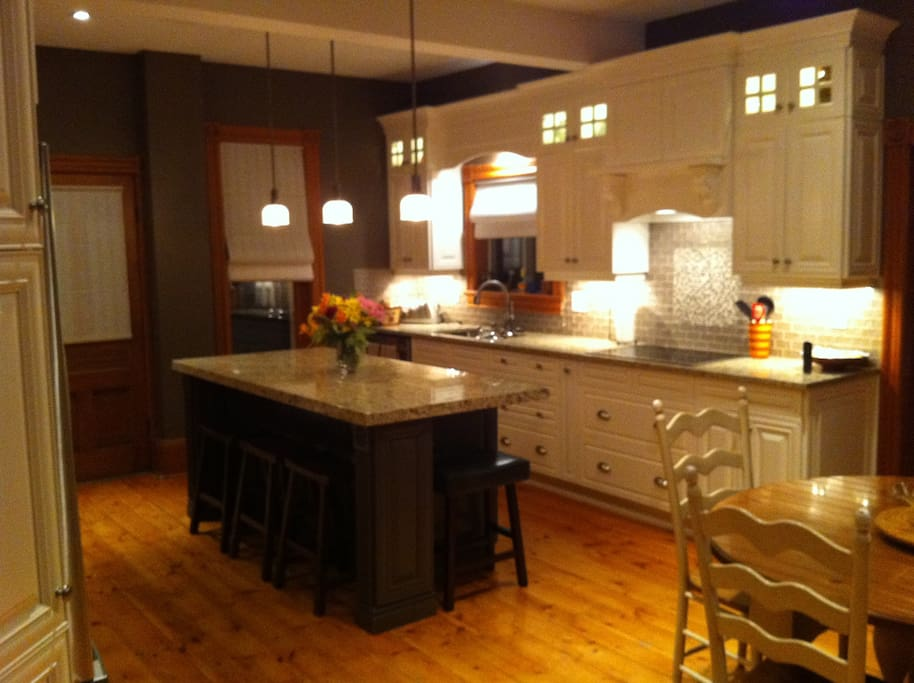 Spacious kitchen custom cabinetry and pine floors