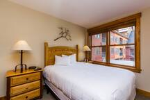 The guest bedroom features a queen-sized bed with Ivory White Bedding and a flat screen TV.