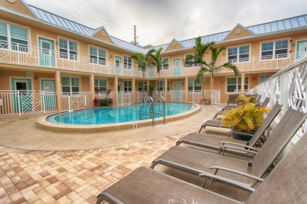 Large Heated Pool with plenty of chaise lounges, and 3 dining tables with umbrella