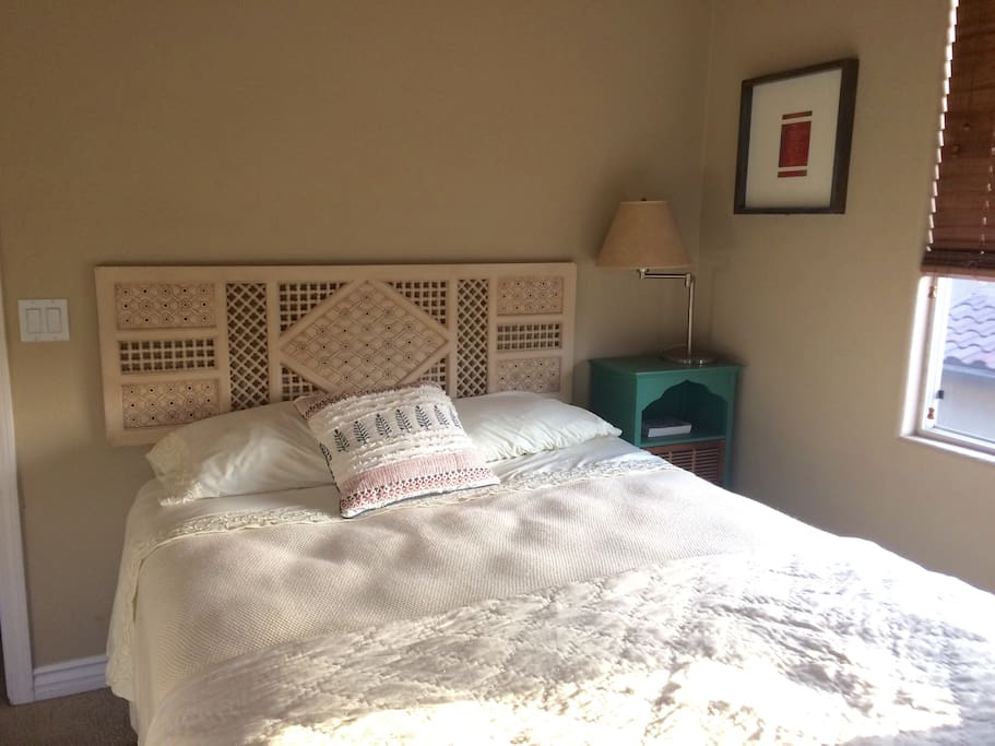 Guest room. Comfy queen bed, end table and lamp. To the left is a large closet with iron, ironing board and mirror.