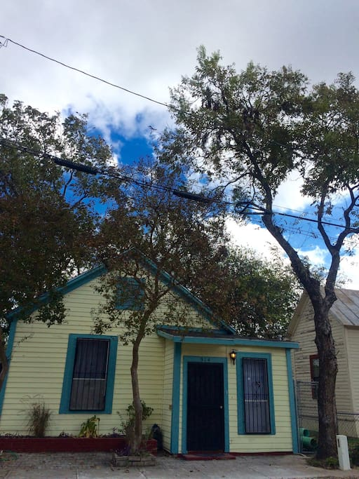Shady cottage is surrounded by crepe myrtles and pecans.