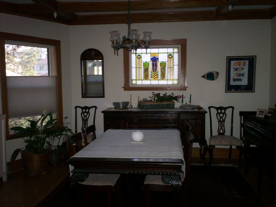 Dining room has original stained glass windows and beamed ceiling
