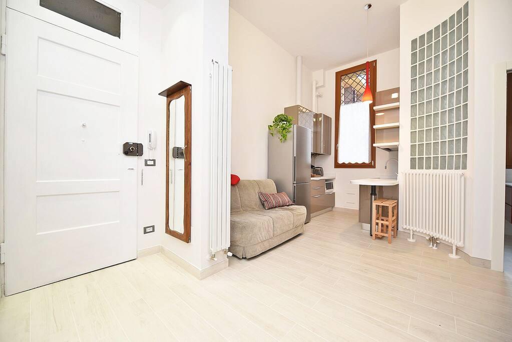 L'ingresso, il soggiorno e la cucina The entrance, the living area and the kitchen