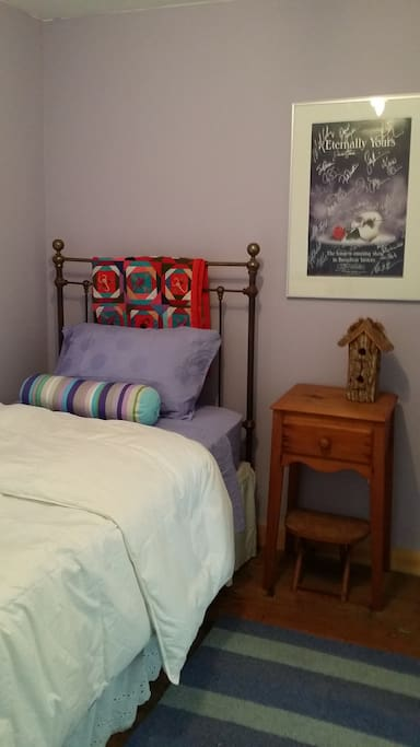 Child's room with antique iron bed. Our nieces picked the purple paint!
