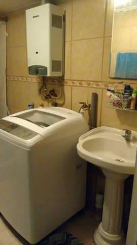 Washing machine offered in the bathroom/Baño con lavadora y agua caliente