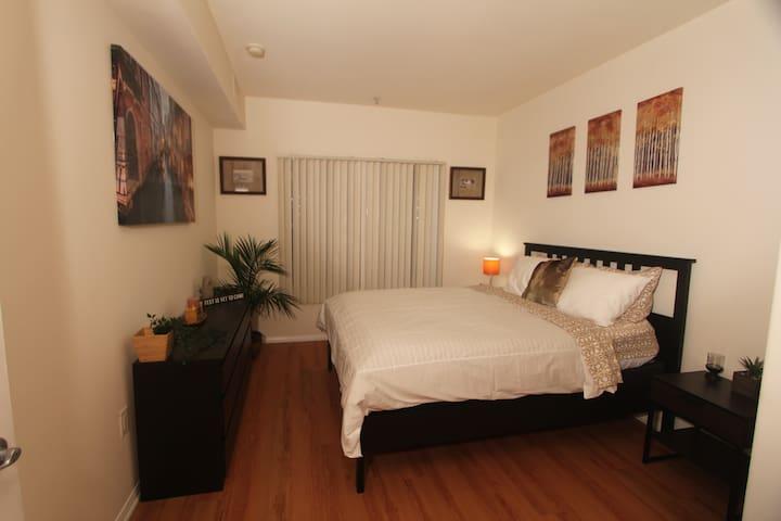 Master Bedroom with Queen Bed, dresser and walk in closet.