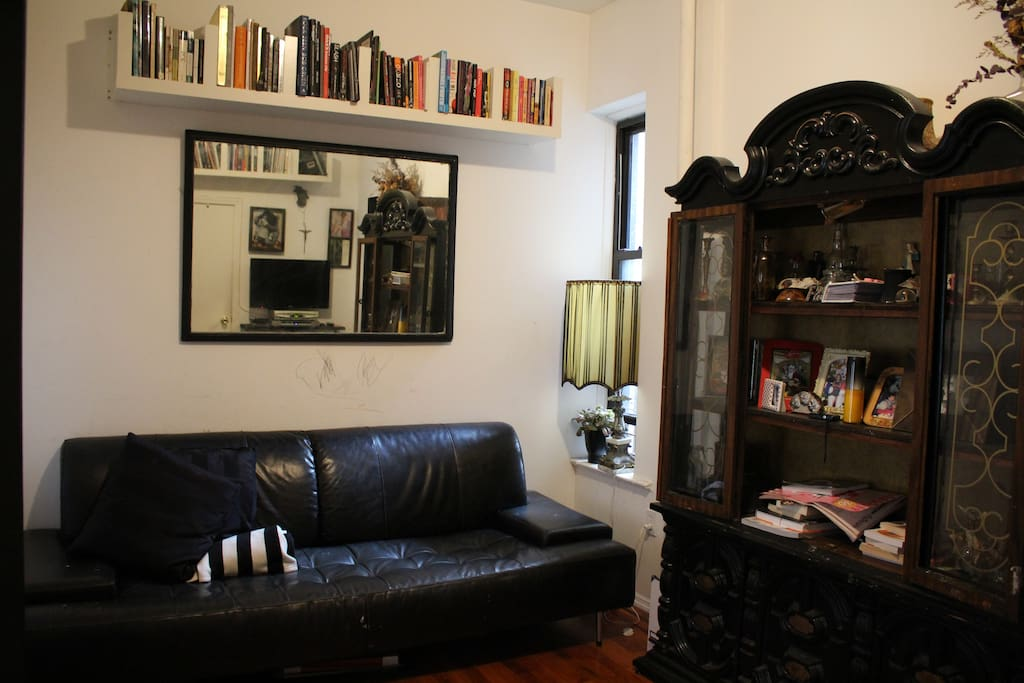 Living room w/Black leather couch, lots of books on music, art, and culture
