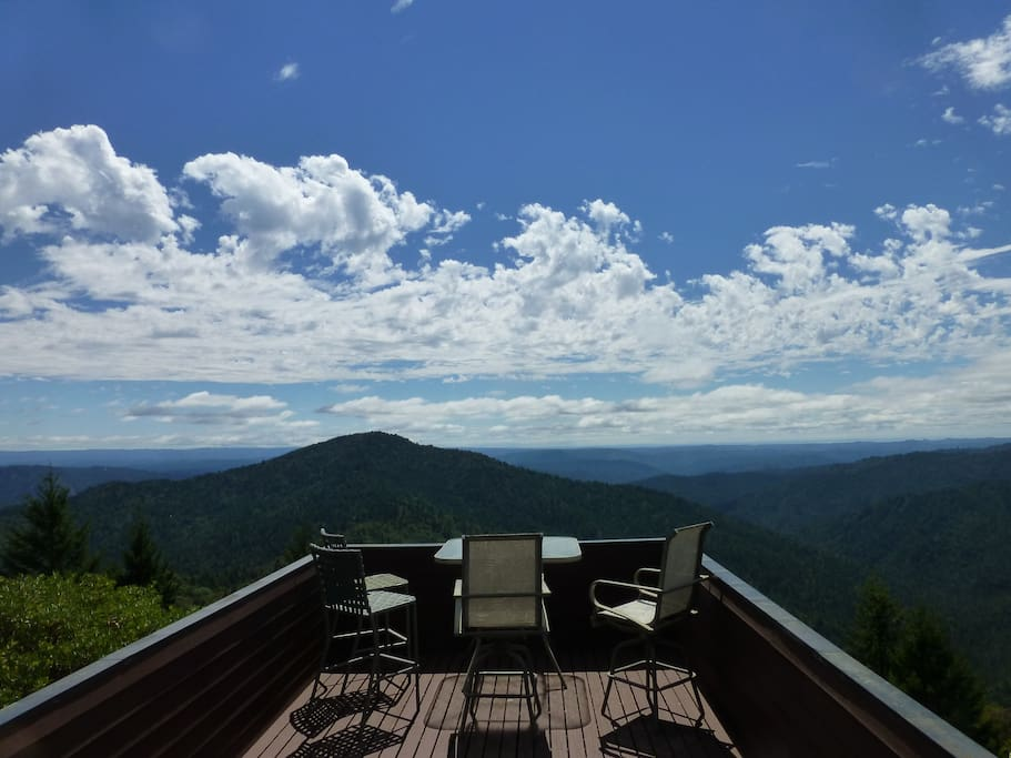 Looking West to the ocean with beautiful clouds. The porch jutting out over the wilderness is a common feature in Frank Lloyd Wright School homes. It is all yours to enjoy, for meals, drinks, skywatching, meditation, reading - your agenda!