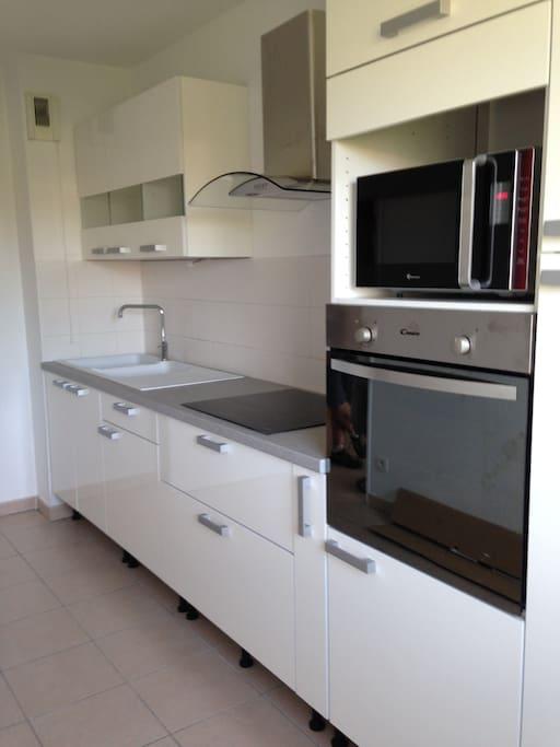 Cuisine toute équipée comprenant four, micro-onde, plaque, hotte, réfrigérateur et congélateur.