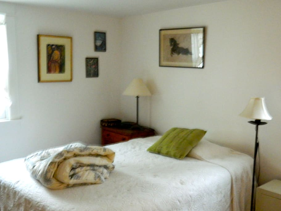Main guest room has a comfy chair, desk, armoire, and a great selection of reading materials