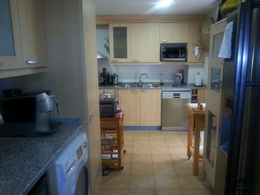 fully-fitted kitchen with two large fridges, washing machine/dryer, dishwasher and microwave oven