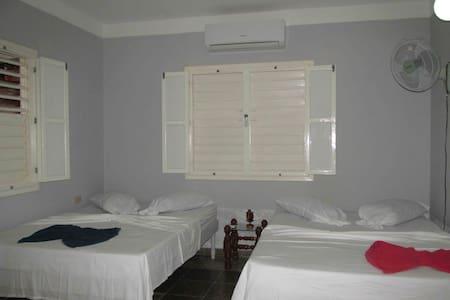 La habitación con dos camas cameras confortables aire acondicionado, ventilador y minibar