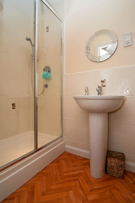 Double shower, pedestal basin and mirror, with electric shaving point.