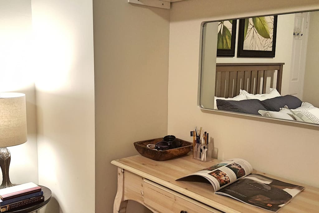 A wall mirror with a small desk for all purposes - make up, work,  readings...etc