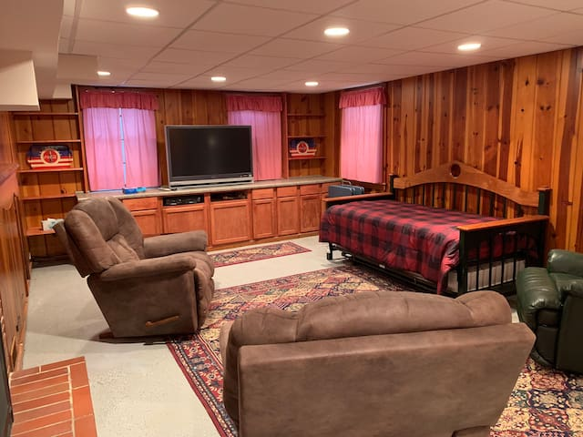 Living area with daybed and trundle — two single mattresses. Egress window is to the right of the big screen tv.
