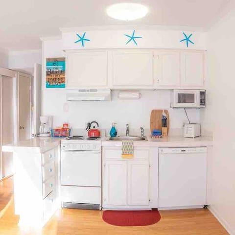Full kitchen with washer, oven, coffee maker, blender & full size fridge